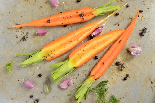 Raw carrots on a baking tray for roasting